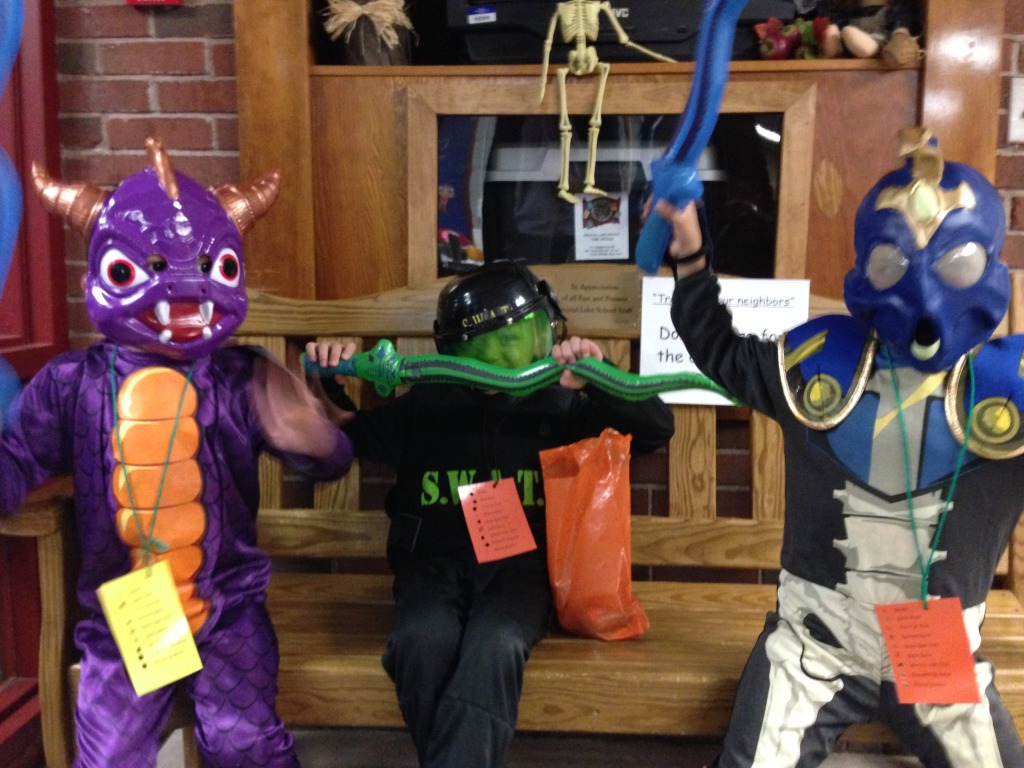 The boys as Skylanders, flanking a friend, at their school Halloween party.