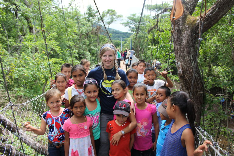Danielle, on the bridge she helped build, with all the children who came to adore her awesomeness while she was there.